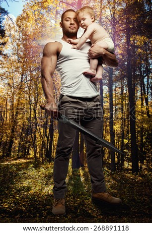 Father hugging a baby and holding a sword over forest background. Conceptual photo, parental protection.   - stock photo