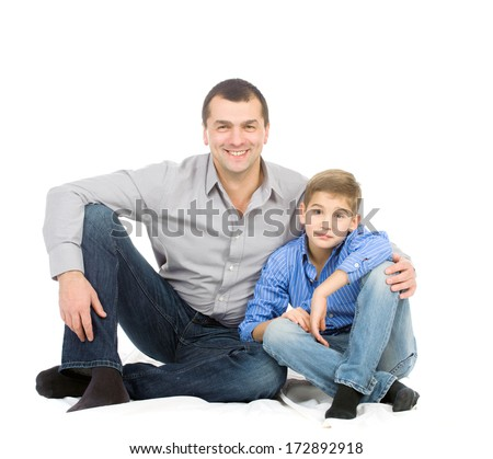 Father hugging her son sitting on the floor. Studio photo on white background.