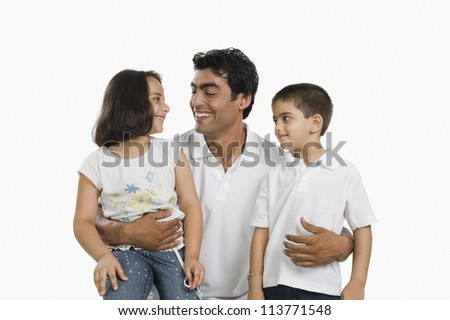Father hugging his children and smiling - stock photo