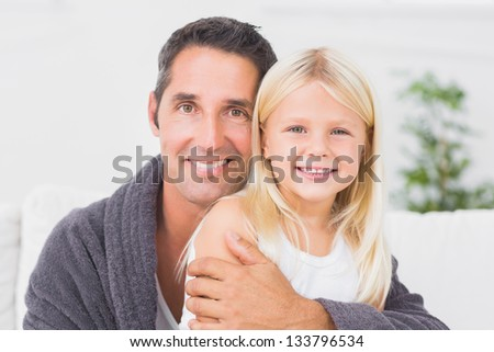 Father hugging his daughter and looking at camera - stock photo