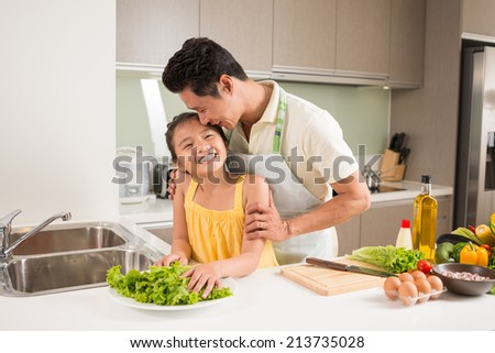 Father hugging his daughter in the kitchen, they are cooking dinner