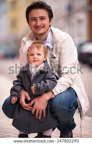 Father hugs his daughter on the street. A little one year old girl stands back to her father. A young man smile to the camera - stock photo