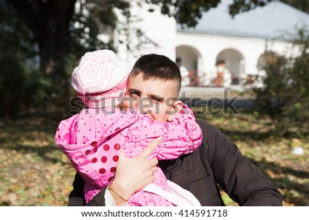 father hugs his little daughter outdoors in city - stock photo