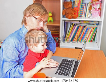 father in business style with little son working on laptop at home - stock photo