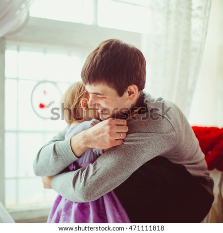 Father in grey pullover hugs his little daughter tightly
