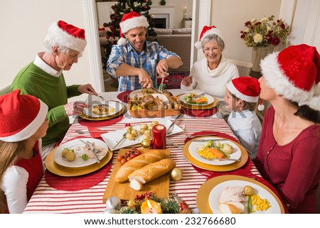 Father in santa hat carving roast turkey at christmas at home in the living room - stock photo