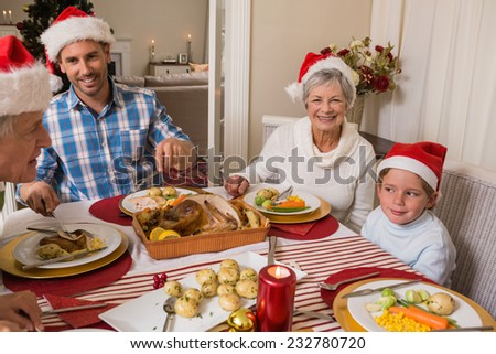 Father in santa hat serving roast turkey at christmas at home in the living room - stock photo