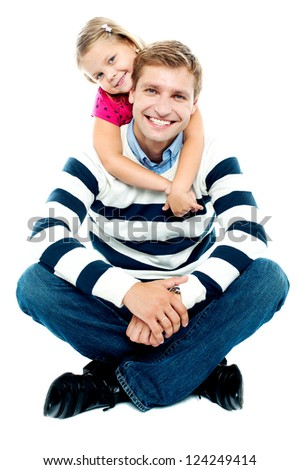 Father in winter wear sitting on the floor with his legs crossed and his daughter holding him from behind - stock photo