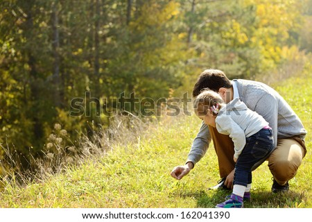 father introducing toddler daughter to the world of nature - stock photo