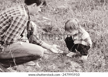 father introducing toddler daughter to the world of nature and showing little lizard - stock photo