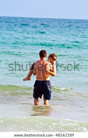 father is carrying his son with the arms at the beautiful sandy beach