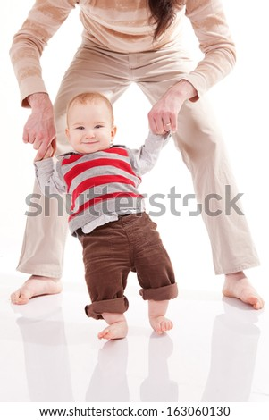 Father is helping his son to make first steps - stock photo