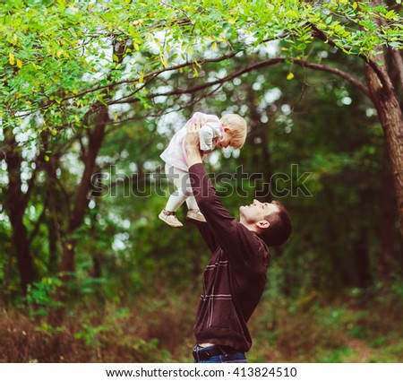 Father is holding a happy baby in the forest