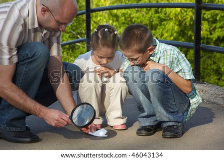 father is using magnifier to burning paper. his son and daughter is looking at this process. focus on left father's knee - stock photo