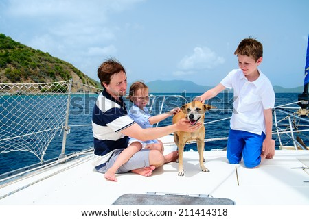 Father, kids and their pet dog sailing on a luxury yacht or catamaran boat - stock photo