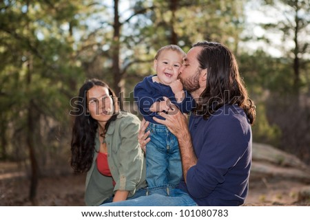 Father kissing baby boy, mother sitting in the background. Shallow DOF, focus on baby.