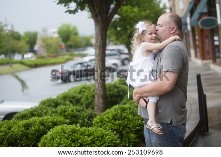 father kissing daughter outdoors at mall