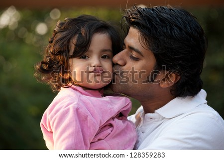 father kissing his daughter, indian man with his one year old daughter