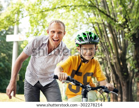 Father learn his son to ride bicycle - stock photo