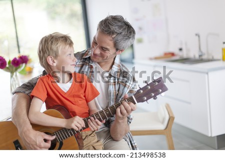 father learning his boy to play guitar - stock photo