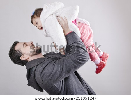 Father lifting his baby daughter up in the air with winter clothes in studio shot