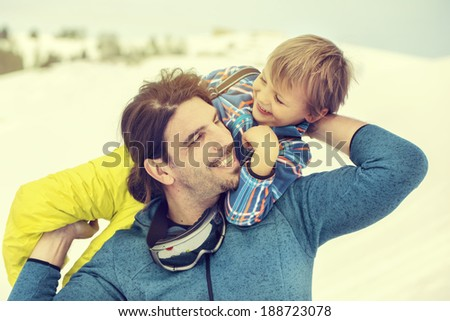 father lifting his son affectionately in the snow with tenderness