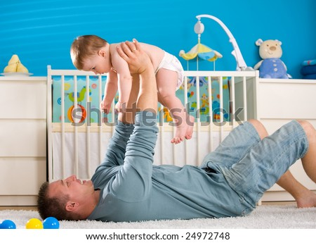 Father lying on back and lifting baby boy ( 1 year old ) at home in children's room. - stock photo