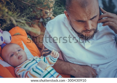 Father lying on the lawn with a baby and talking on the phone. - stock photo