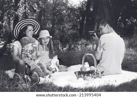 Father makes photos of his family on picnic - stock photo