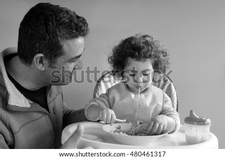 Father (man age 35-45) takes care of his child (girl age 2-3) at meal time. Fatherhood, parenting and childhood concept. Real people copy space