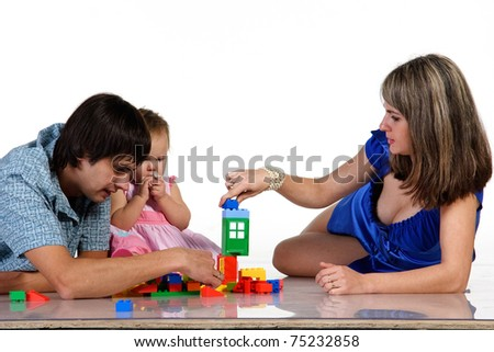 father, mother and baby is playing together and building of blocks. Isolated on white