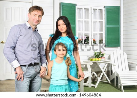 Father, mother and cute little daughter stand next to new house with green shutters. - stock photo