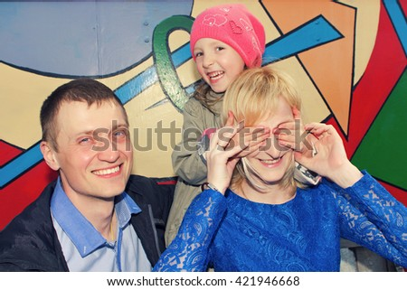 Father, mother and daughter making a joke or playing hide and seek. Family, hide, seek, family, hide, seek, family, hide, seek, family, hide, seek, family, hide, seek, family, hide, seek, family, hide - stock photo