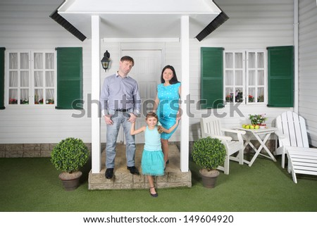 Father, mother and daughter stand near porch of their new house. - stock photo