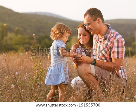 Father mother and daughter walking on the field - stock photo
