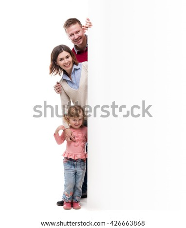 father, mother and little daughter peek out from behind empty blank isolated on white background