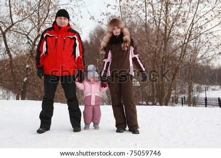father, mother and little daughter standing at snow at winter, focus on girl