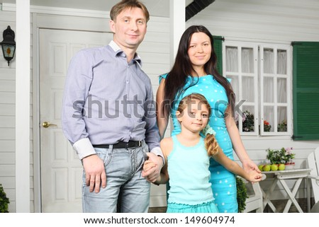 Father, mother and pretty little daughter stand next to new white house. - stock photo