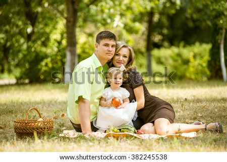father, mother and small daughter resting in a park cheerful and happy sitting on the grass, run.
