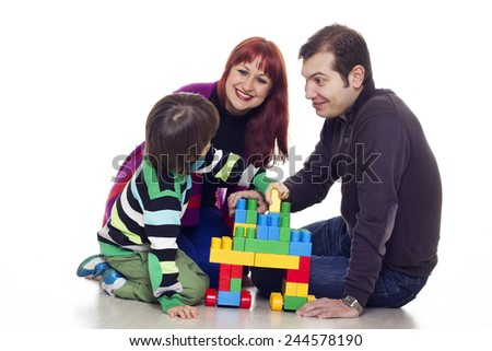 Father, mother and son playing lego over white background - stock photo