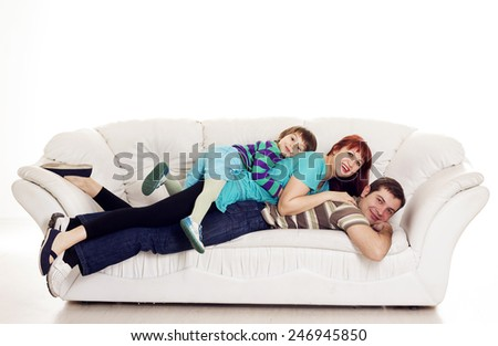 Father, mother and son resting on the sofa over white background - stock photo