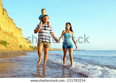 Father, mother and son walking along a beach on sunset. Summer vacation - stock photo