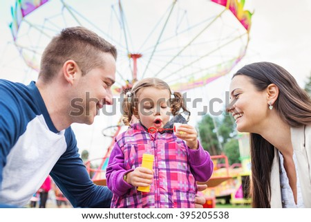Father, mother, daughter blowing bubbles, amusement park, fun fa - stock photo