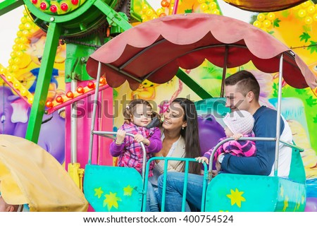 Father, mother, daughters enjoying fun fair ride, amusement park - stock photo