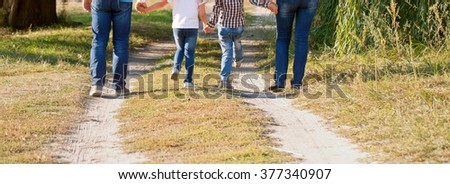 Father, mother, son and daughter walking along the path. Family feet and legs in jeans. Rear view.