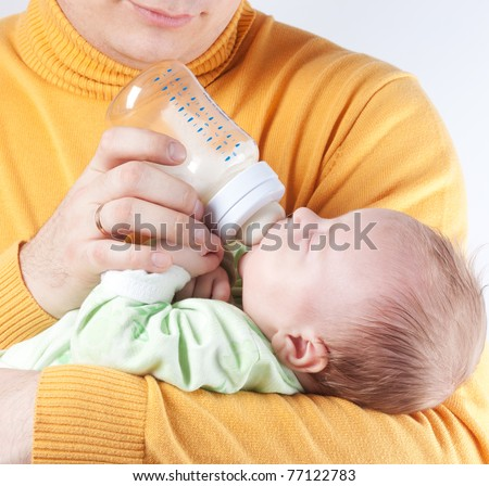 Father nurse new born baby from bottle with milk