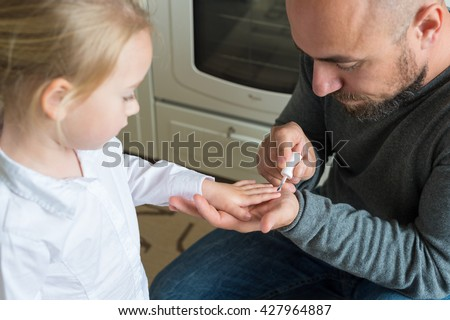 Father painting little daughters finger nails