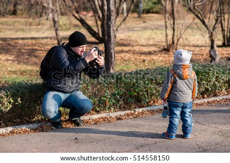 Father photographing son in the Park