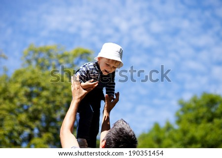 Father picking up smiling toddler in the park - stock photo