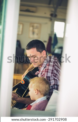 Father  playing guitar for son at home